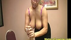 Chesty mature tugging a junior mans cock
